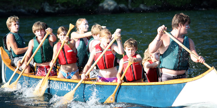 Kids paddle in a canoe race