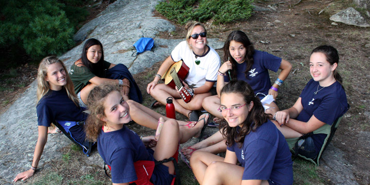 Counselor playing guitar with campers