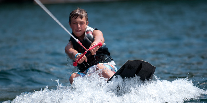 A camper learns to wakeboard on Lake George
