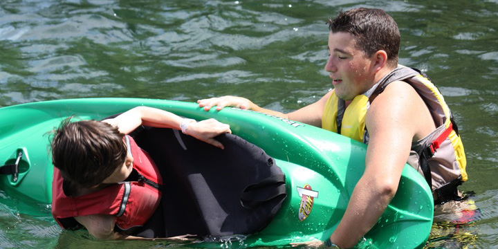 A Counselor Helping a Camper Kayak at Coed Camp
