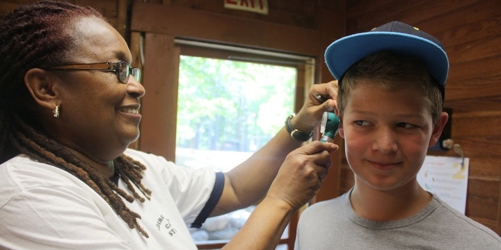 A Nurse Taking Care of a Young Camper at Co-Ed Camp